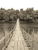 Old wooden bridge over river — Stock Photo