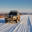 Stock Photo: Winter road with car 4x4