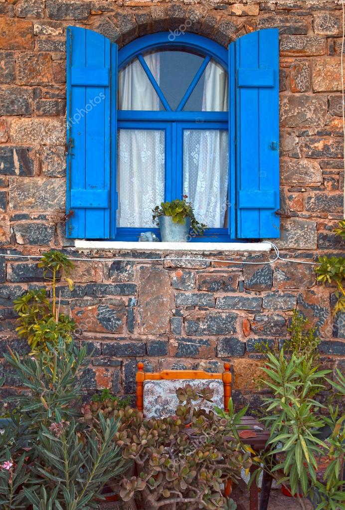 Vintage blue window with shutters on old stone wall and flowers , Crete, Greece. vertical image — Stock Photo #14495431