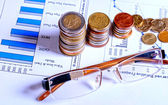 Glasses and coins on financial graphics — Stock Photo