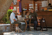 Two Greek men sit at a rustic outdoor cafe(Crete,Greece) — Stock Photo