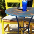 Outdoor restaurant with blue table and yellow chair (Greece) — Stock Photo #19548891