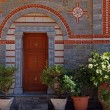 Door entrance and flower pots in beautiful greek monastery(Greec — Stock Photo