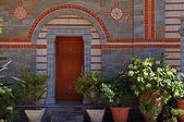 Door entrance and flower pots in beautiful greek monastery(Greec — Stock fotografie