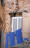 Old wall, window and blue linen (Italy) — Stockfoto