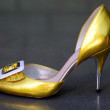 Golden female stiletto — Stock Photo