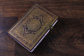 Old ornate notebook on wood background — Stok fotoğraf