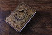 Velho caderno ornamentado em fundo madeira — Foto Stock