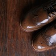Luxury brown shoes on wood background. — Stock Photo #23139692