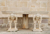 Medieval table with caryatids — Stock Photo