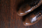 Luxury brown shoes on wood background. — Stock Photo