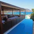 Outdoor cafe, resort pool and Mediterranean sea (Crete, Greece) - Stock Photo