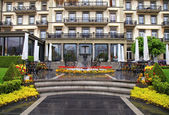 Fountain and flowers in front of beautiful building(Switzerland) — Stock Photo