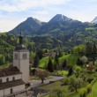 Church and Alps mountains, Gruyeres, Switzerland — Stock Photo #28128641