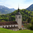 Church and Alps mountains, Gruyeres, Switzerland — Stock Photo