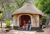 Sotho couple wearing tribal handmade dress sitting near traditio — Stock Photo