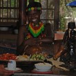 African smiling young woman in tribal restaurant, Lesedi, Africa — Stock Photo