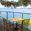 Table and iron chairs on terrace with sea view (Greece) — Stock Photo