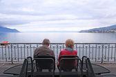 Senior man and woman relaxing at lake Geneva, Switzerland — Stock Photo