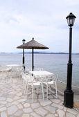 Beyaz masa, sandalye ve şemsiye üzerinde deniz i̇skelesi, yunanistan. — Stok fotoğraf