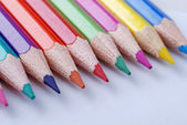 Multicolored crayons in a row on white background. — Stock Photo
