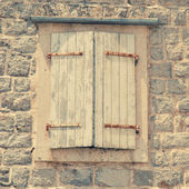 Closed window with shutters in old rough stone wall of ancient i — Stockfoto