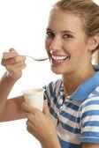 Joven mujer comiendo yogurt — Foto de Stock
