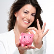 Young beautiful woman standing with piggy bank money box — Stock Photo #19666553