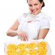 Young pretty woman showing homemade fresh pasta — Stock Photo #19671613