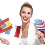 Beautiful woman showing international flags — Stock Photo #22528975