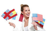 Beautiful woman showing international flags — Stock Photo