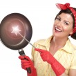 Young beautiful woman housewife showing a magic wand on dishes — Stock Photo