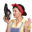 Beautiful vintage housekeeper holding  a smelly shoes with facia — Stock Photo