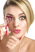 Close up of a funny beautiful girl using eyelash curler — Stock Photo