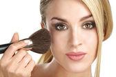 Beautiful model applying professional make up using a brush — Stock Photo