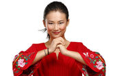 Chinese woman greeting gesture in elegant red dress — Stock Photo