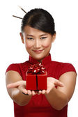 Traditional asian girl showing a christmas gift — Stock Photo