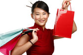 Beautiful asian woman showing multicolor shopping bags — ストック写真