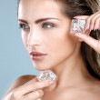 Beautiful woman applying ice cube treatment on face — Stock Photo #41570327