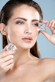 Beautiful woman applying ice cube treatment on face — Stock Photo