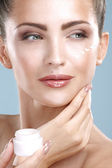 Beautiful woman applying cream treatment on her perfect face — Stock Photo