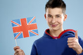 Young smiling male student teenager holding a flag — Stock Photo