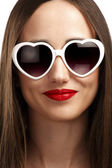 Young smiling girl with heart-shaped glasses — Stockfoto