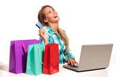 Online alışveriş masa başında oturan genç kadın — Stok fotoğraf