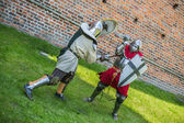 Armored fighting knights with medieval castle in the background — Stock Photo