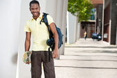 Portrait of a balck student with skateboard and bag — Stock Photo