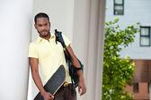 Portrait de jeune homme noire avec la planche à roulettes et un sac — Photo