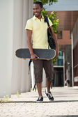 Young man with a skateboard and bag over his shoulder — Stock Photo
