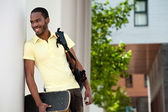 Portrait of a black man with skateboard and bag — Stock Photo