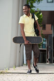 Black man with skateboard and bag — Stock Photo